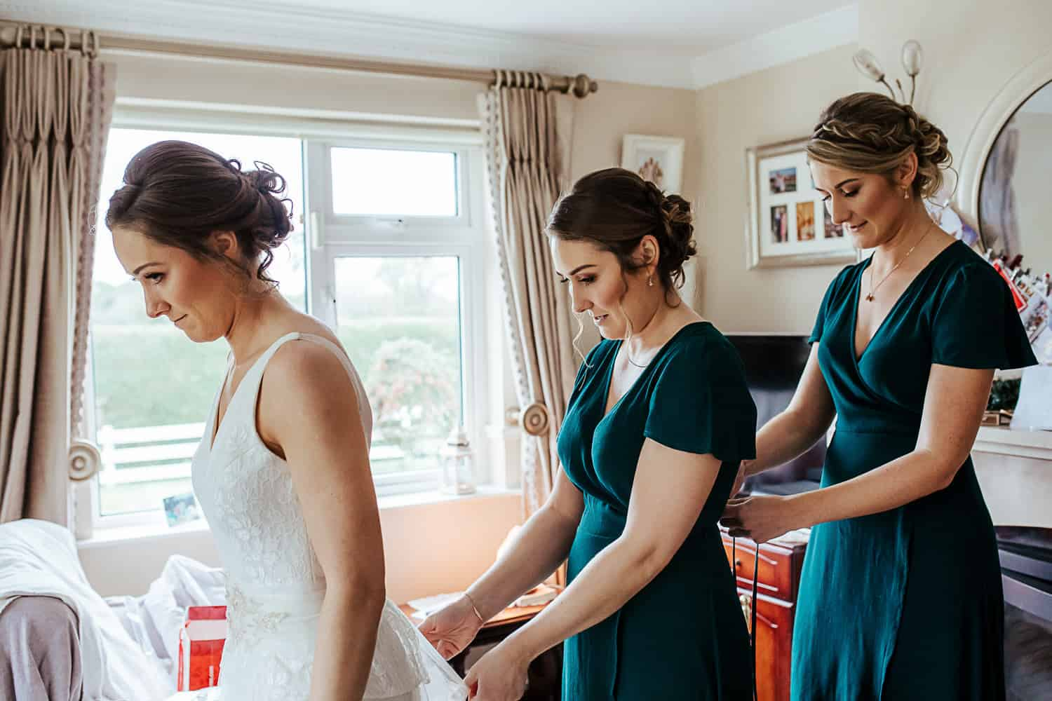 bridesmaids helping bride get into her wedding dress