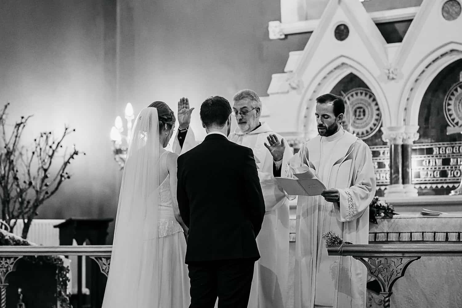 priests giving blessing to wedding couple