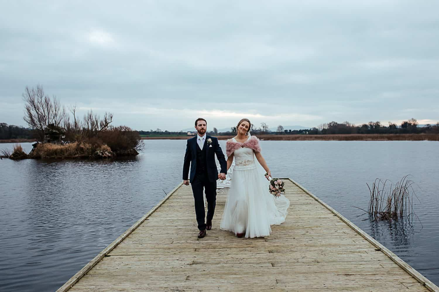 bride and groom walking on the pier at ashley park house wedding