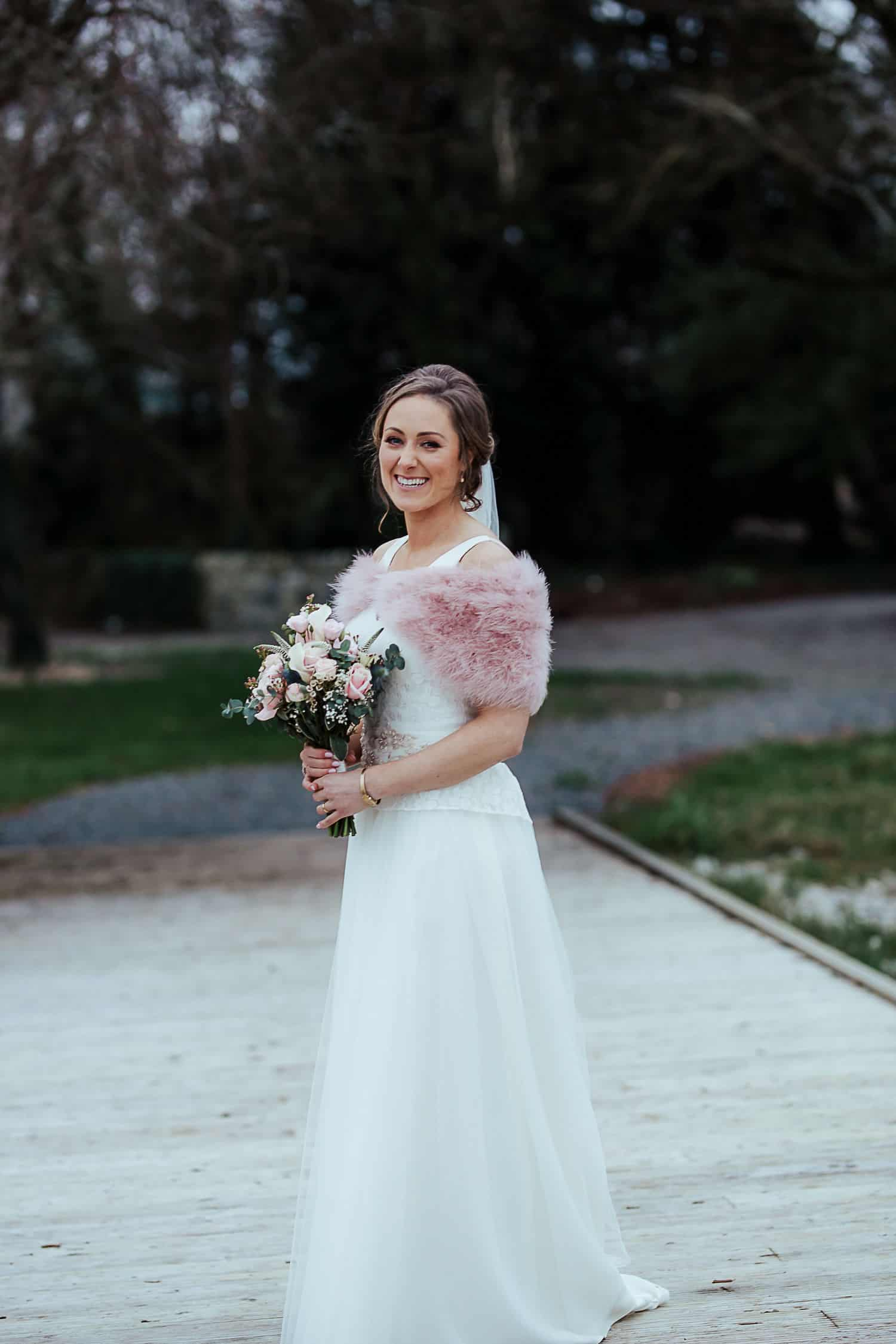bride in pink ostrich winter coat ashley park house wedding