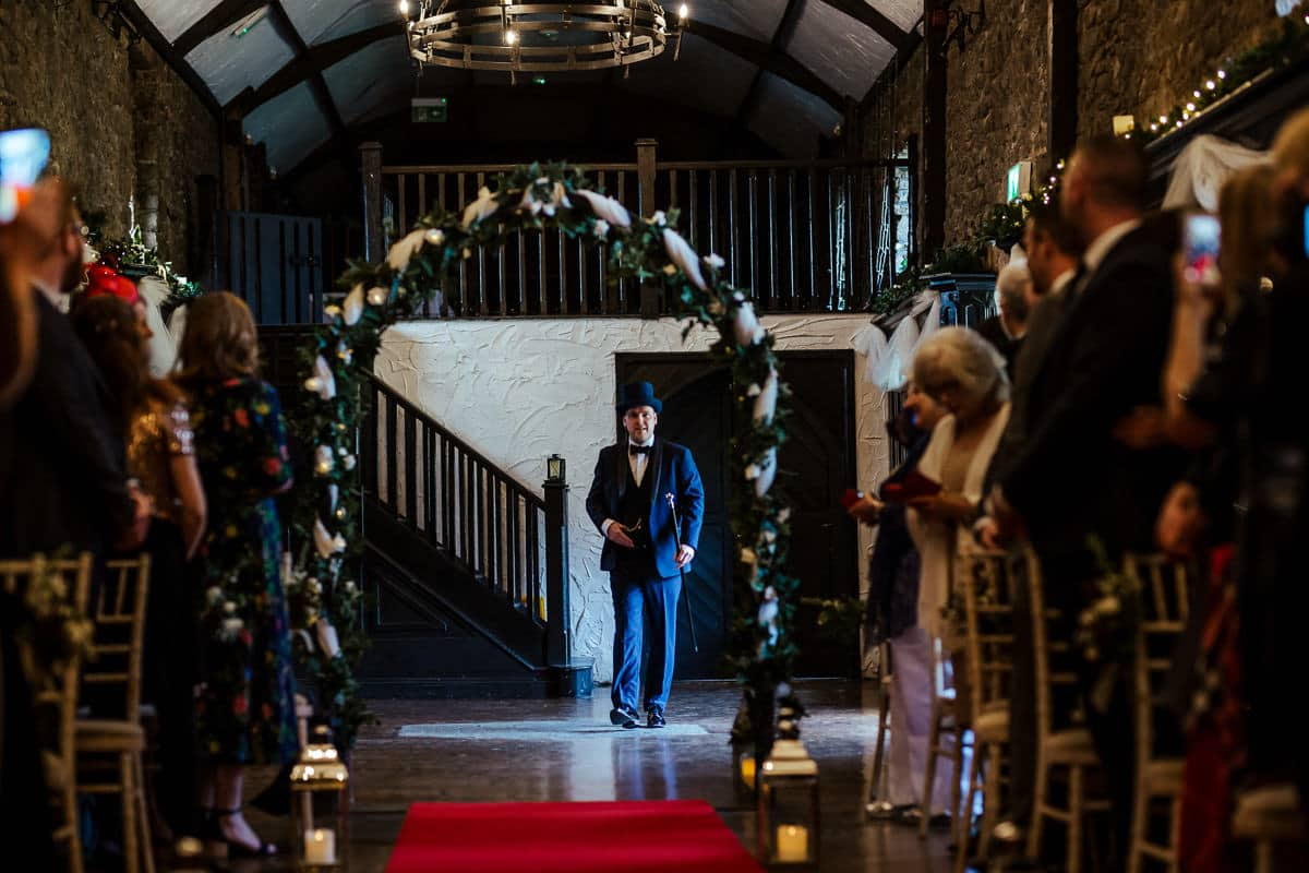 groom in three piece suit and top hat walking up the aisle at kinnity castle wedding