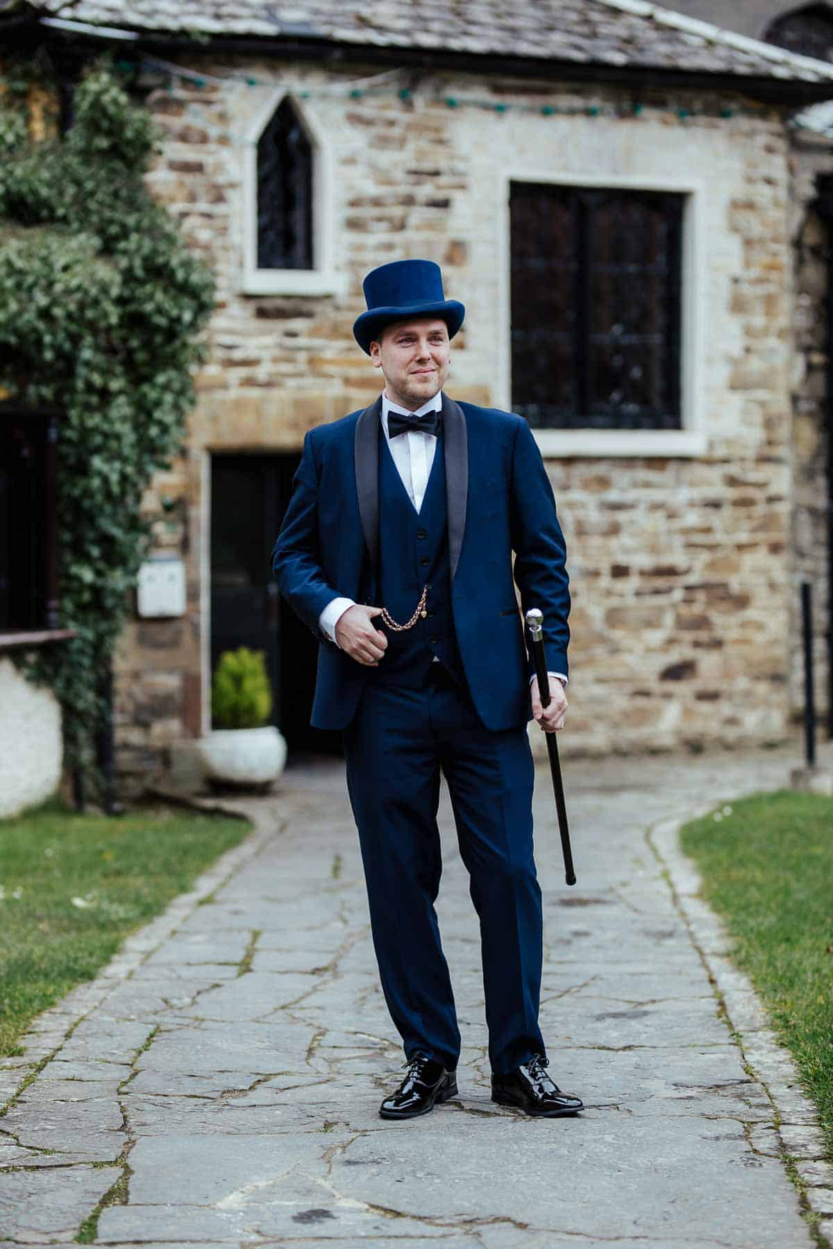 groom in navy suit bow tie top hat cane vintage wedding style