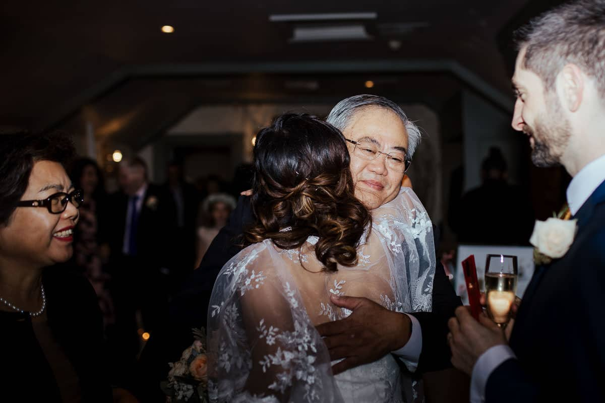 father of the bride hugging his daughter after wedding ceremony