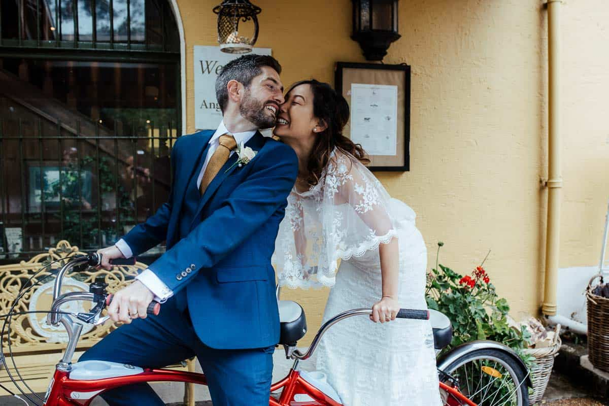 bride and groom on tandem bicycle at wrights anglers rest wedding