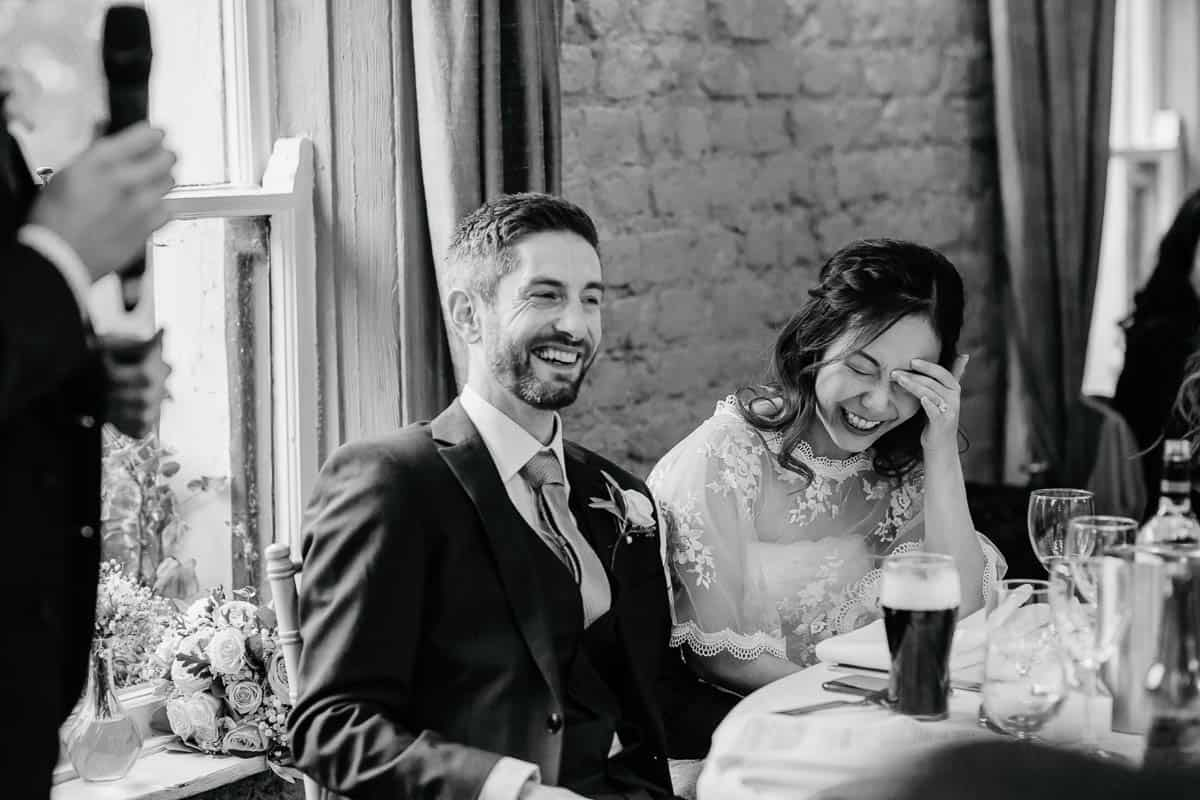 bride and groom laughing during wedding speeches at wrights anglers rest dublin