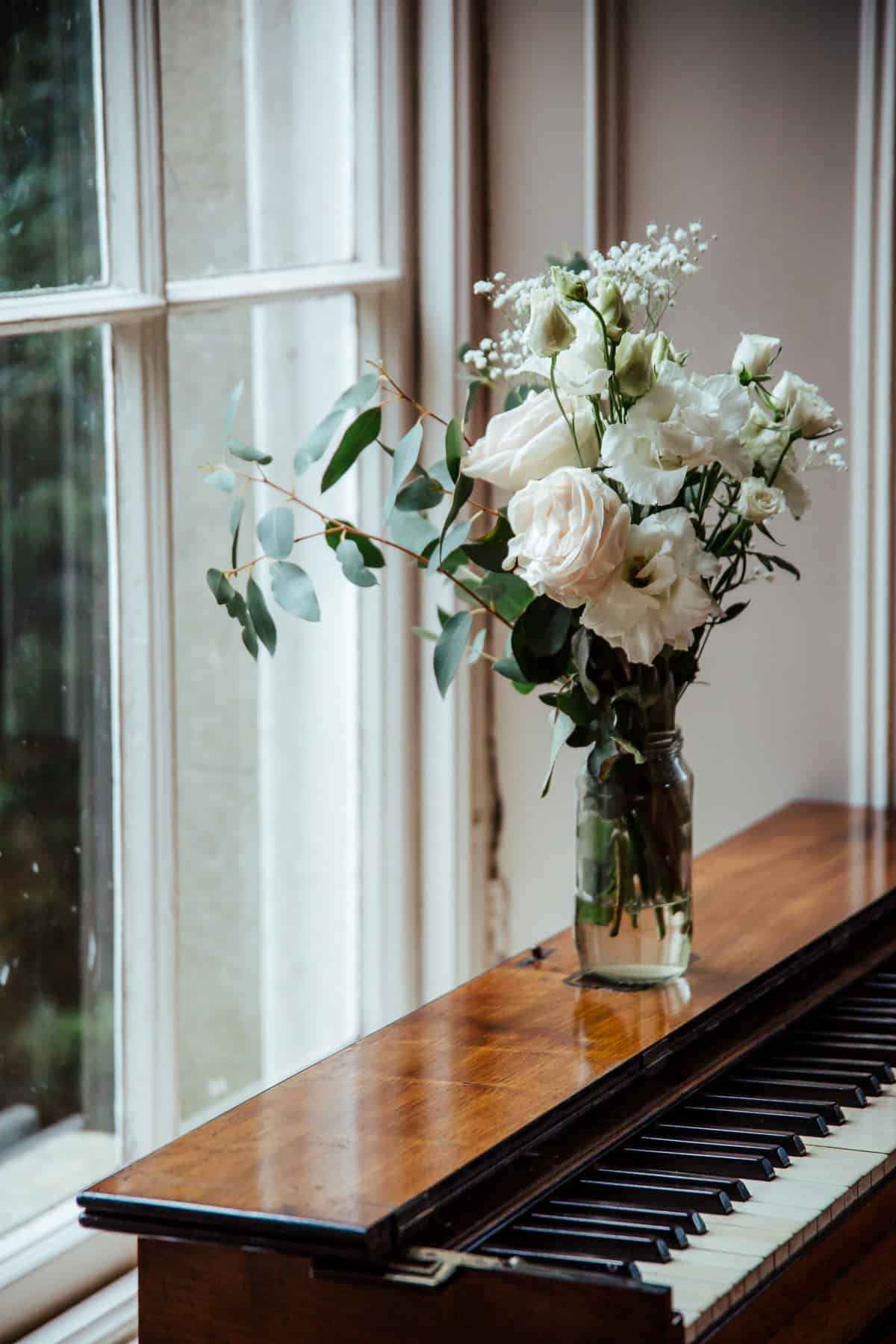 bouquet of white roses on a piano in manor house