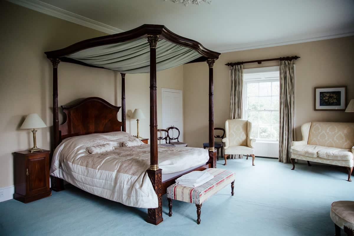 white master bedroom in trudder lodge wedding venue