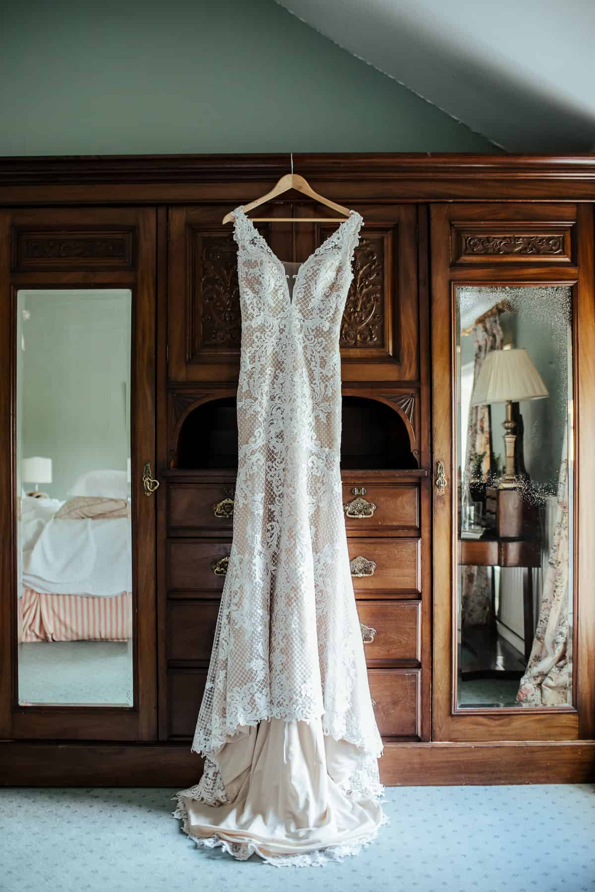 nude wedding dress with lace hanging on a vintage wardrobe