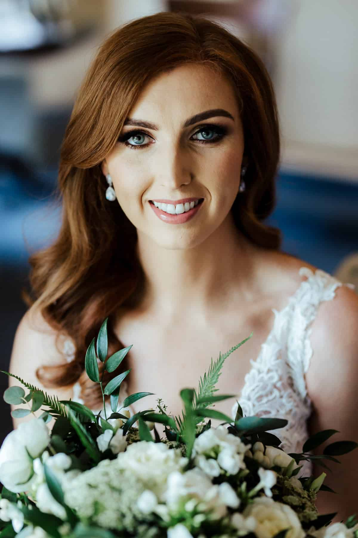 bride in a nude dress with white and green bouquet