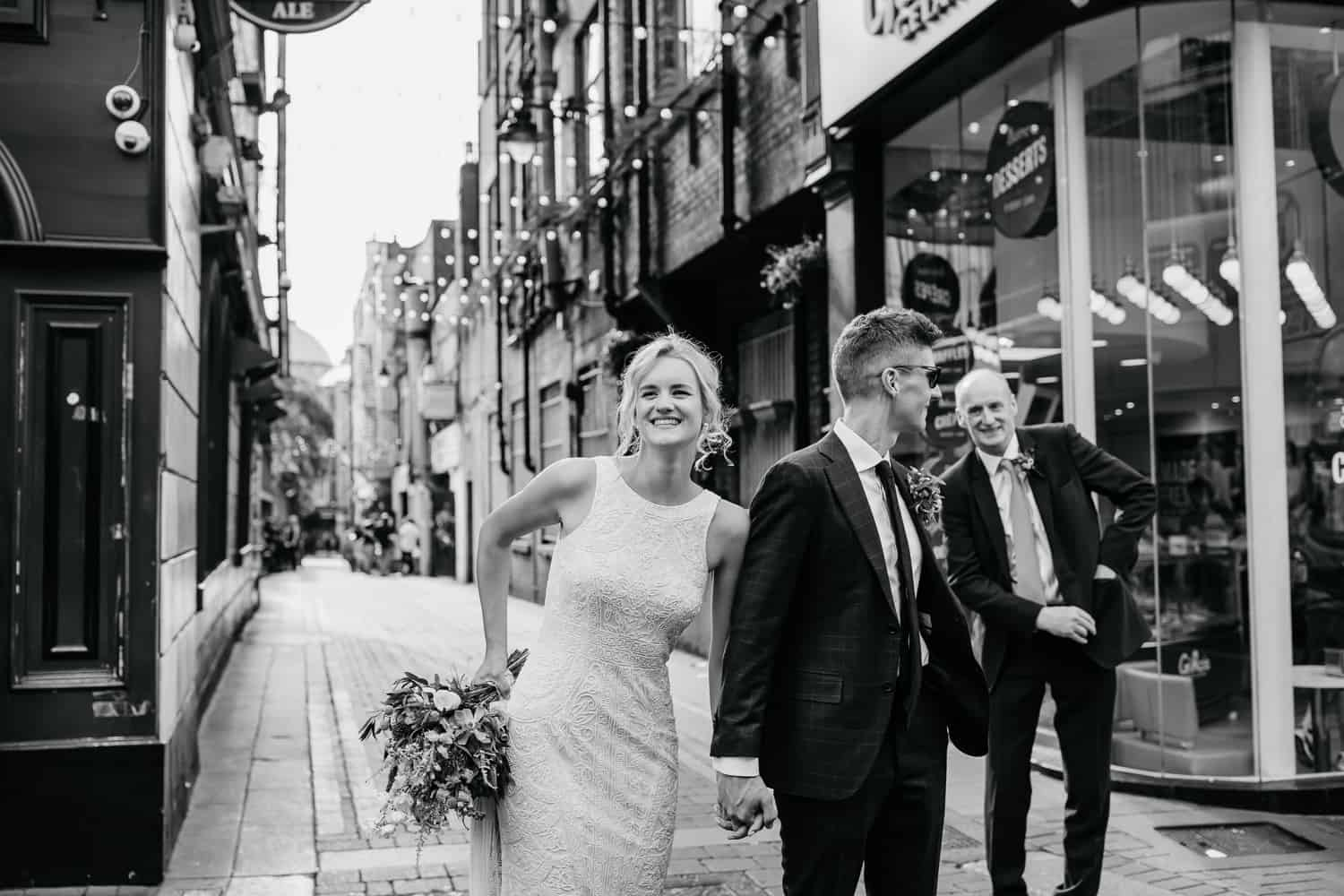 bride and groom walking through the streets of dublin