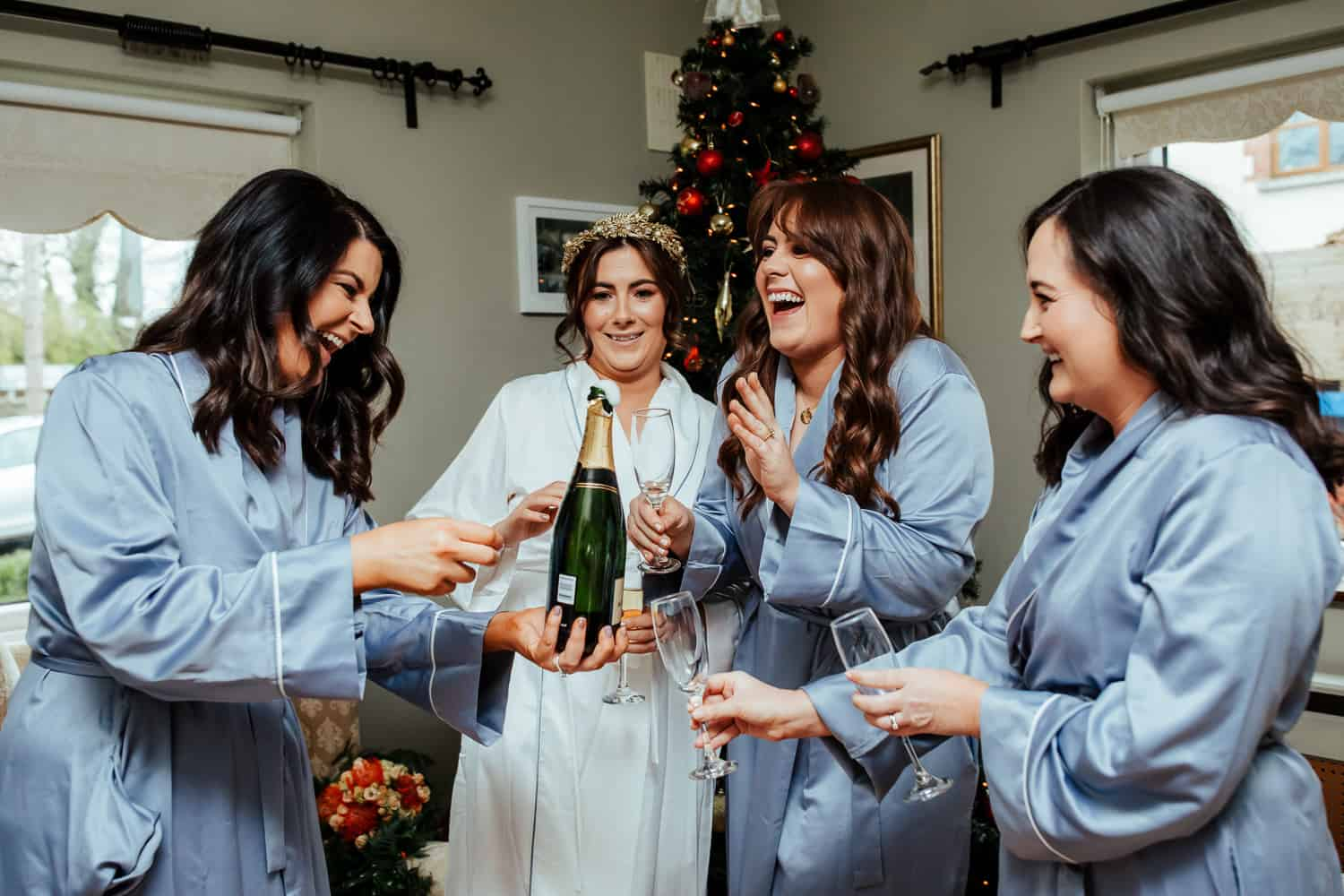 bride and bridesmaids having a prosecco toast the morning of the wedding
