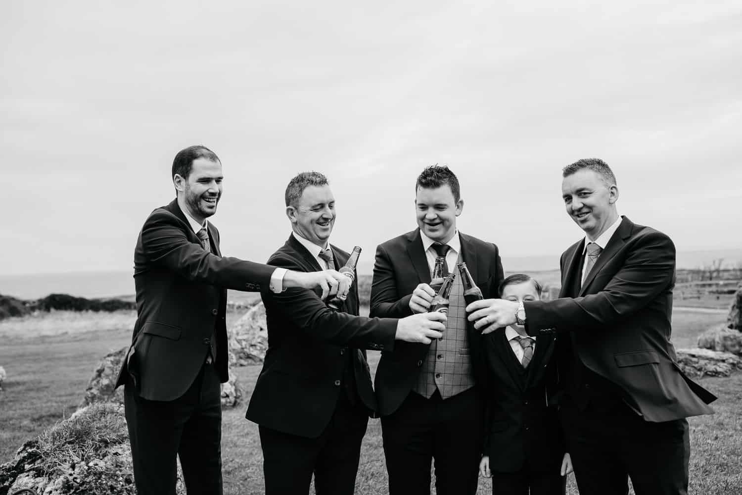 groom and his groomsmen enjoying a beer personalized beer bottles