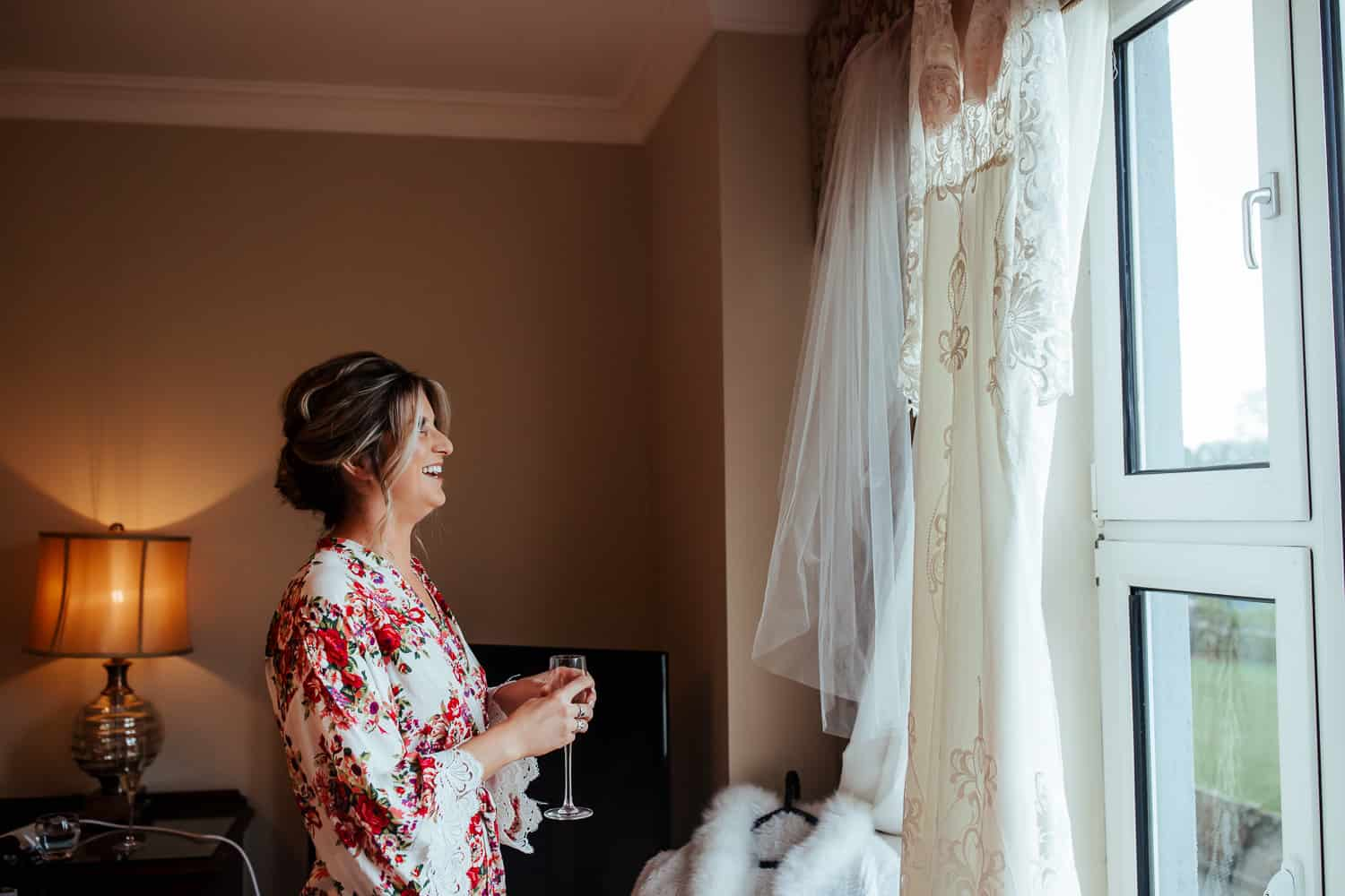 bride looking at her wedding dress on wedding morning